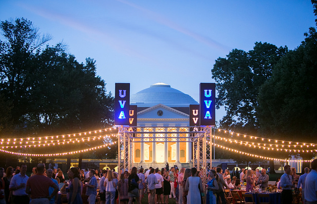 Reunion event held on UVA's lawn, complete with a large crowd, beautiful lights, banners, and a stunning sky in Charlottesville, VA