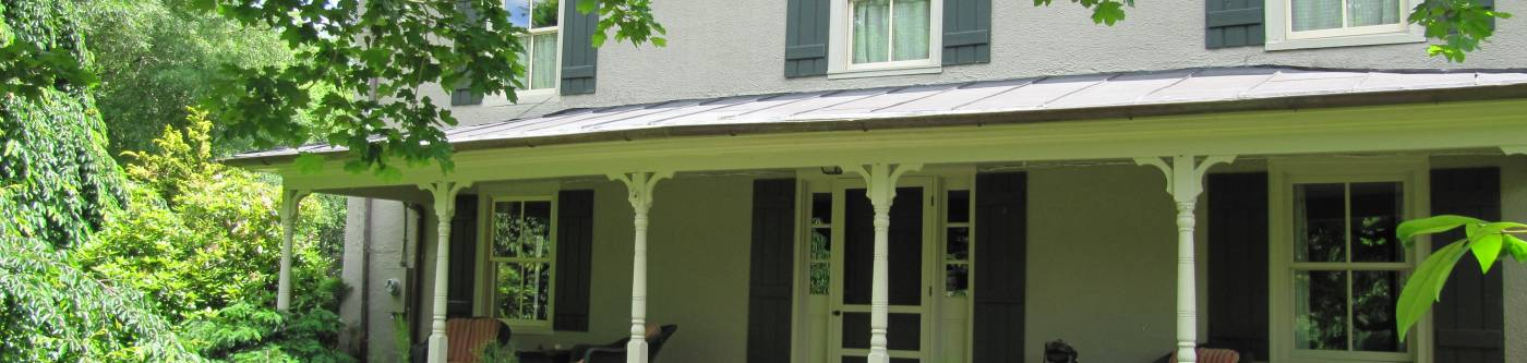 The front of a beautiful country home in Charlottesville, with vibrant green surroundings for extended stay accommodations